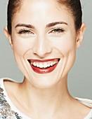 Lachende brünette Frau in Paillettenshirt, Lippen dunkelrot geschminkt (Close Up)