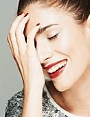 Lächelnde brünette Frau in Paillettenshirt, Lippen dunkelrot geschminkt, hält Hand vor Gesicht (Close Up)