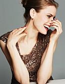 Lachende brünette Frau in Paillettenshirt hält Hände an Hals und Nase