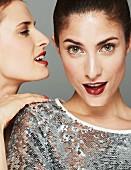 Zwei dezent geschminkte Frauen mit roten Lippen, etwas ins Ohr sagen (Close Up)