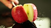 An apple being sliced in half