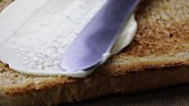 Butter being spread onto a slice of toast and left to melt (close-up)