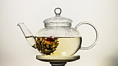 Tea with flowering tea in a glass jug