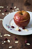 A baked apple filled with almonds and dried cranberries