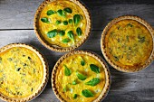 Four cheese quiches with herbs (seen from above)