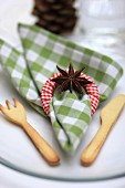 Christmas place setting with linen napkin, napkin ring, star anis and pastry cutlery