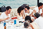 A bride and groom and guests eating by the sea