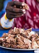 Massai-Krieger isst Nyama Choma (gegrilltes Fleisch, Tansania)