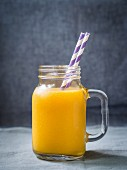 Exotic, yellow fruit smoothie in a glass jar with a paper straw