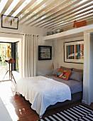 weiße Tagesdecke auf Doppelbett in offenem Schlafbereich, oberhalb Glasdach mit Holzlamellen Abdeckung