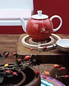 Red teapot on spiral birchwood trivet
