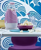 Kultige Popcornmaschine in Lila auf Esstisch, im Hintergrund Stoffbahn mit blau-weißem Wellenmotiv