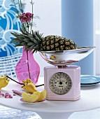 Rosa Retro-Küchenwaage und Glasvase auf rundem Tisch