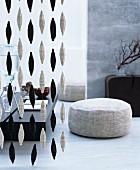 Wohnraum im fernöstlichen Stil in Grau und Schwarz mit Bodenkissen und dekorativem Zimmervorhang