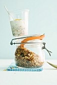A cup of muesli on a jar of cereals
