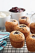 Friands with cherries on a wire rack