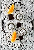 Vegan chocolate orange truffles on white lace cloth (seen from above)