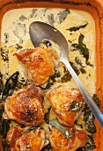 Oven-baked chicken thighs in a creamy kale sauce