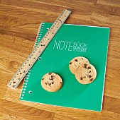 Chocolate chip cookies on a notebook with a ruler