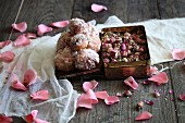 Sweet cakes with icing and rose petals