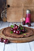 Chocolate crepes with cherries on a wooden plate