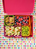Pasta salad, beans, berries and crackers in a lunch box