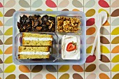 A sandwich, dried fruit, crispy muesli and yoghurt in a plastic box