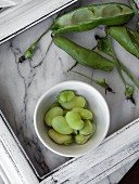 Fresh fava beans in a white bowl