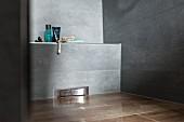 Ausschnitt einer bodenebenen, grau gefliesten Dusche, mit Wandablauf in schmaler Vormauerung, Badutensilien