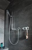 Duschbereich grau gefliest mit Handbrause an Duschstange und Armatur