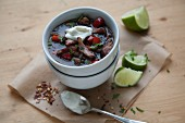 A bowl of chilli con carne with peppers and sour cream