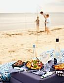Strandpicknick mit Salat, Häppchen und Getränken