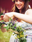 Frau bindet Blumenkranz fürs Mittsommerfest