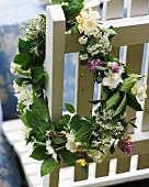 Blumenkranz auf Gartenstuhl als Deko zum Mittsommerfest