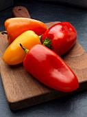 Red, yellow, and orange peppers on a wooden chopping board