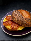 Scrambled egg and bacon on a poppy seed roll for breakfast