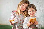 Two little girls eating sandwiches