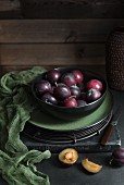 Fresh plums in a black bowl