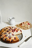 Plum cake, sliced, and a jug of cream