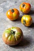 Four organic tomatoes on a stone surface