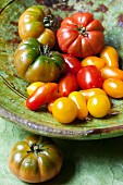 Various organic tomatoes in a ceramic bowl