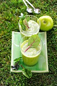 Two green smoothies garnished with lettuce and apple in the garden