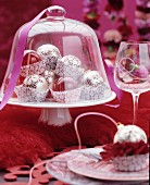 Festive table arrangement of Christmas tree baubles in paper cake cases under glass cover