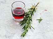 A glass of red wine and a sprig of rosemary
