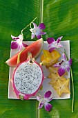 An arrangement of melon, pitahaya, star fruit and orchid flowers