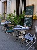 Gedeckte Bistrotische vor Hauswand eines Cafes