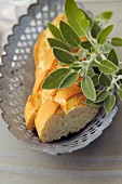 Sliced baguette in a metal dish garnished with sage leaves