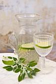 Wasser mit Limettenscheiben in Krug und Glas
