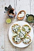 Spicy corn tartlets with a green sauce and cheese
