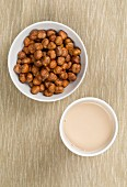 A cup of hazelnut milk and a bowl of hazelnuts